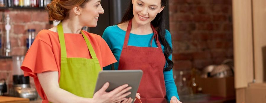 Two women in a cooking class use a tablet.